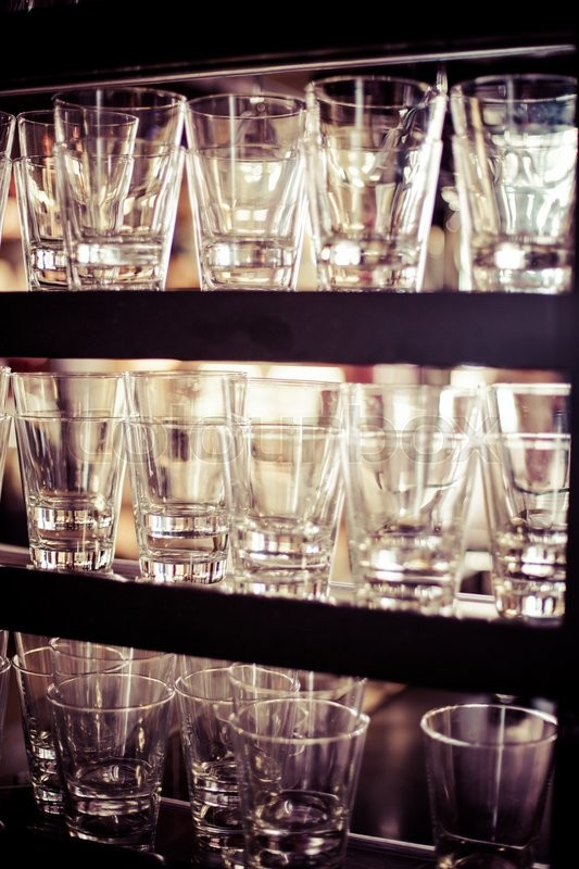Empty glasses for wine above a bar rack , stock photo