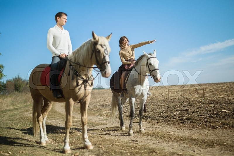 Young couple in love riding a horse walking on the background of autumn nature in a beautiful field. Girl shows something guy hand in the field, stock photo