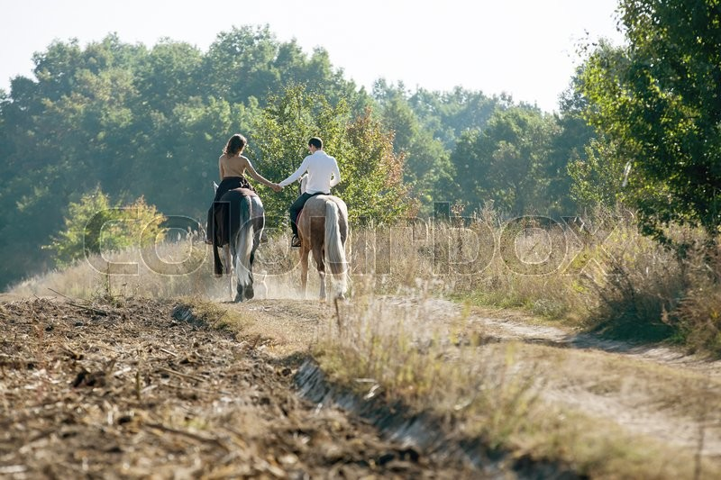 Young couple in love riding a horse walking on the background of autumn nature in a beautiful field. Couple pretty hold each other\'s hand, stock photo