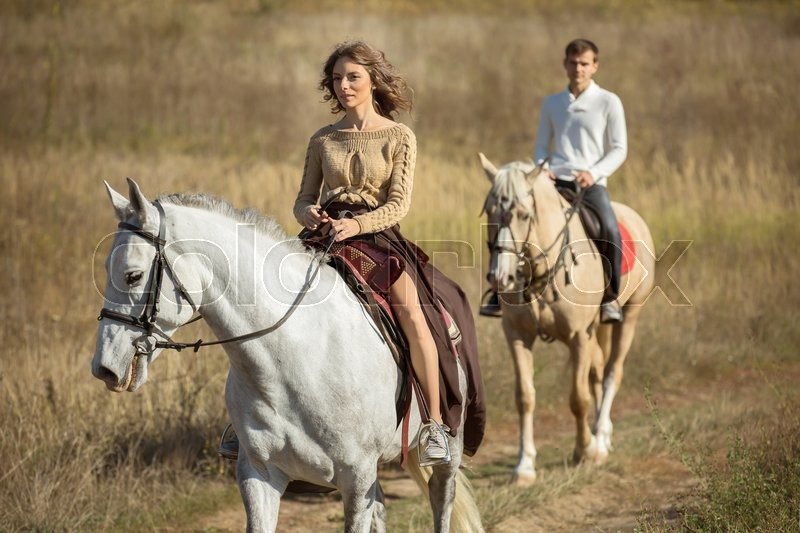 Young couple in love riding a horse walking on the background of autumn nature in a beautiful field, stock photo
