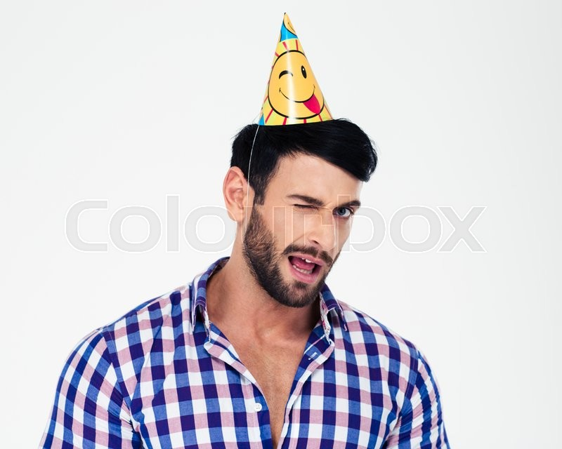 Portrait of a handsome man in birthday hat winking isolated on a white background, stock photo