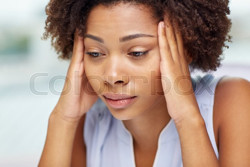 People, emotions, stress and health care concept - unhappy african american young woman touching her head and suffering from headache, stock photo