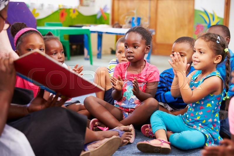 Teacher reading a book with a class of preschool children, stock photo