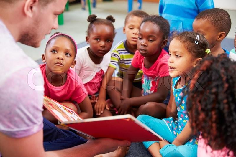 Volunteer teacher reading to a class of preschool kids, stock photo