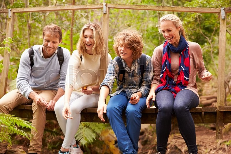 Parents and teens playing, sitting on a bridge in a forest, stock photo
