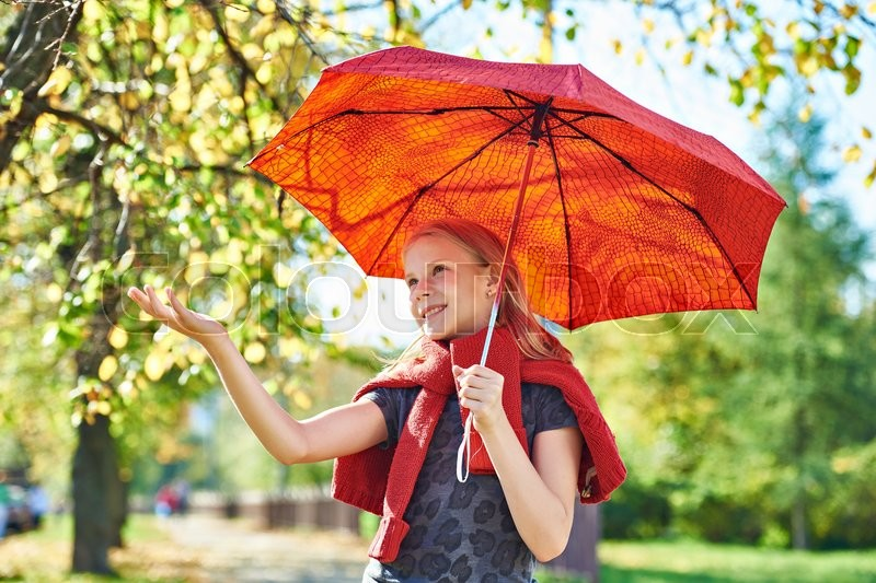 Stock image of 'Joyful girl with a red umbrella in the autumn park on a sunny day'