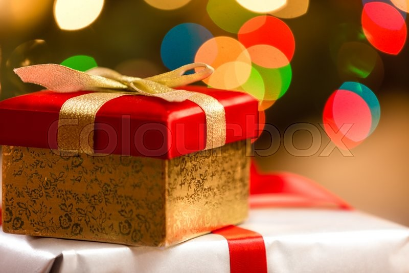Red Christmas box with golden ribbon on background of colorful lights, stock photo