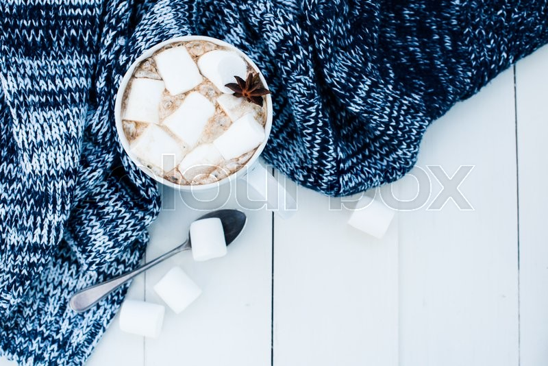 Cozy winter home background, cup of hot cocoa with marshmallow, old vintage books and warm knitted sweater on white painted wooden board background, stock photo