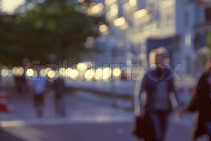 Blurred image of people walking in the street at evening, stock photo