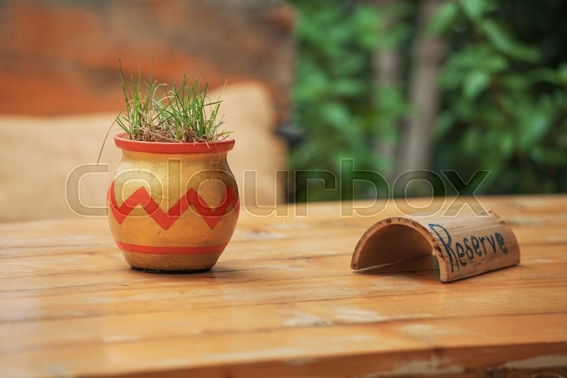 A pot of grass on a wooden table the decoration in the cafe, stock photo