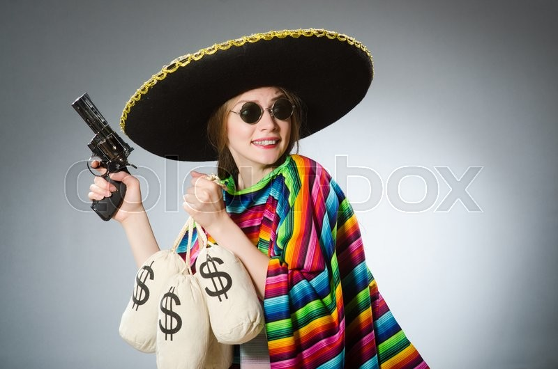 Girl in mexican poncho holding handgun and money sacks against gray, stock photo