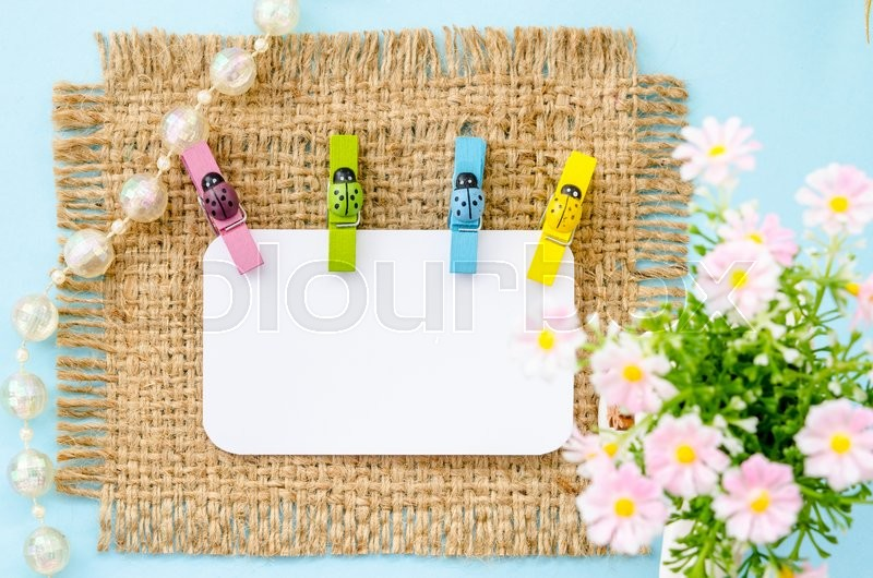 Blank white paper tag and colorful ladybug wooden clamps with flower on sack. For your text, stock photo