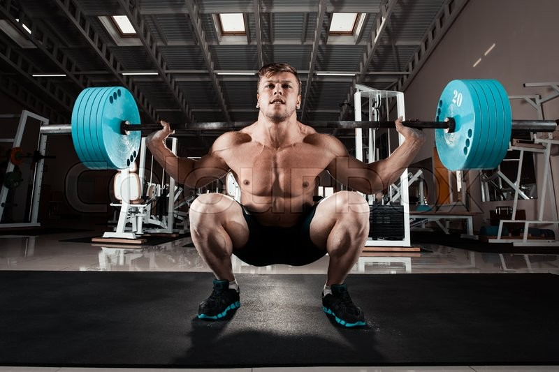 Man at the gym. Execute exercise squatting with weight, in gym, stock photo