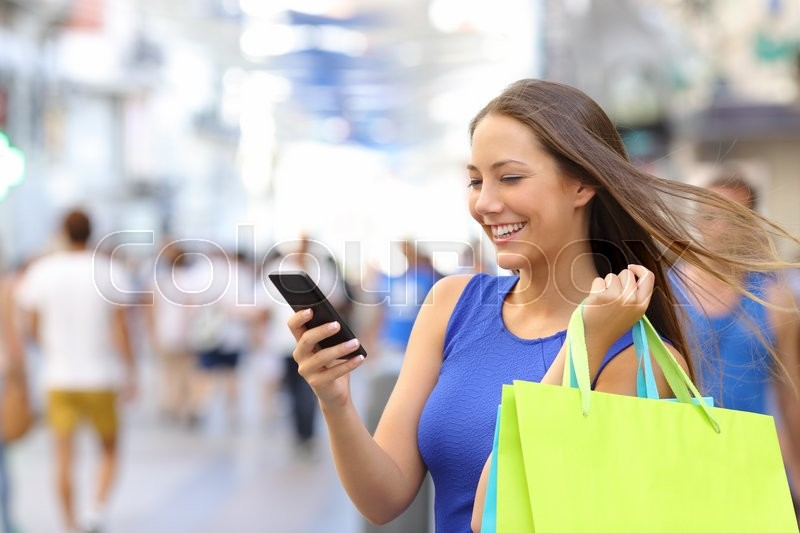 Shopper woman shopping with a smartphone in a commercial street, stock photo