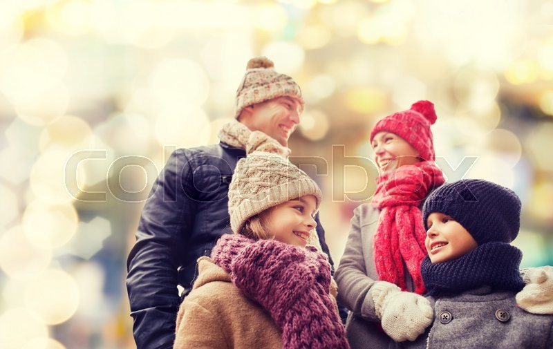 Family, childhood, season, holidays and people concept - happy family in winter clothes over lights background, stock photo