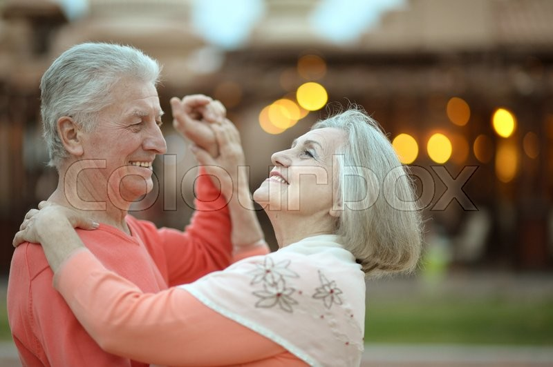 Senior couple resting at the resort during vacation on dance floor, stock photo