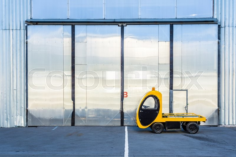 Electric cargo car pickup truck with cargo platform near hangar at the aviation territory. Airfield airport special equipment Forklift. Mini electric cargo truck, stock photo