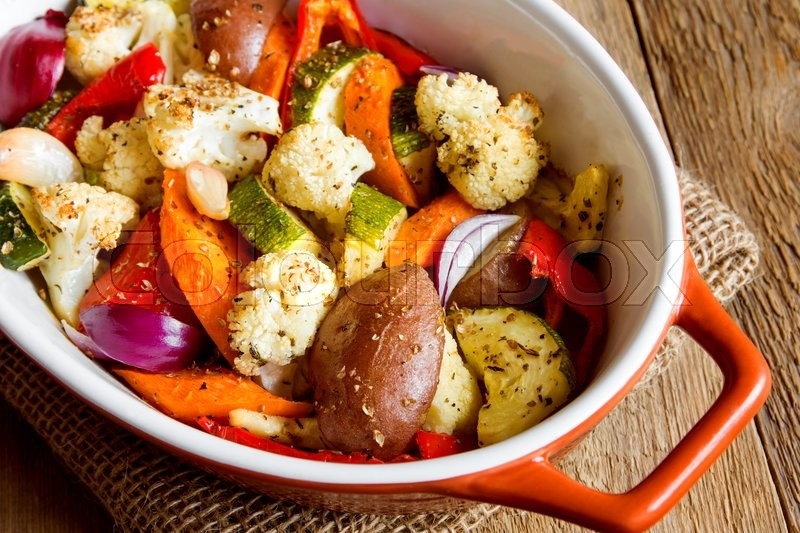 Stock image of 'Rustic oven baked vegetables with spices and herbs in baking dish close up, vegetarian organic meal'