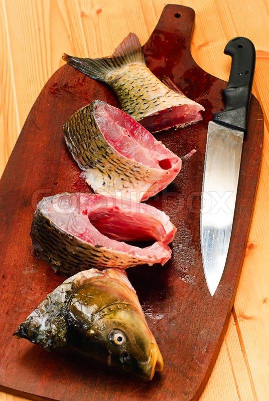 Raw carp fish on a wooden cutting board stock photo for Fish cutting board