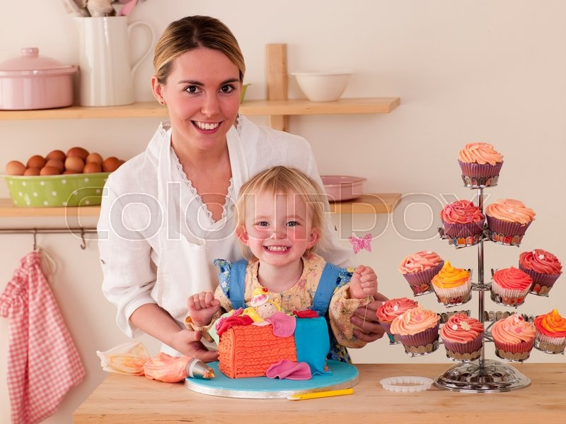 Mother and Daughter decorating cakes together, stock photo
