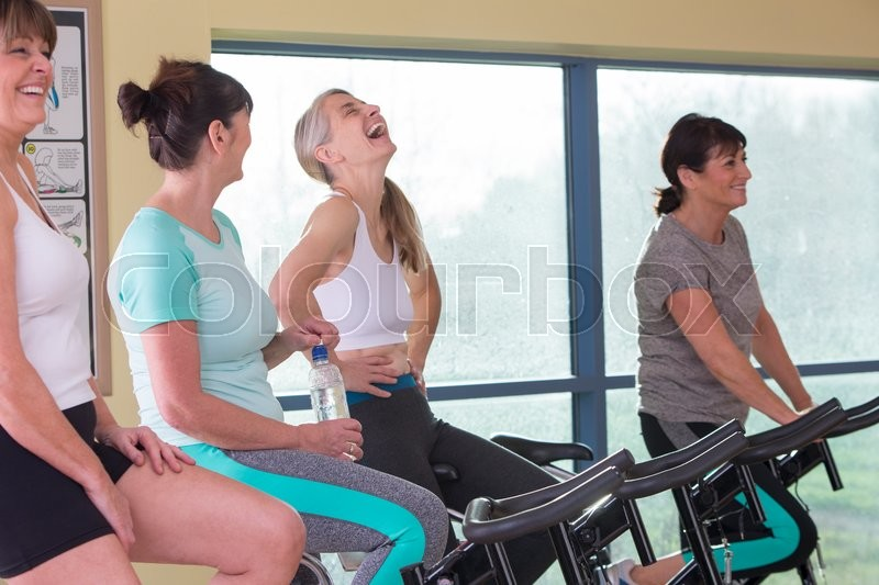A group of senior women enjoying themselves on spinning bikes at the gym, stock photo