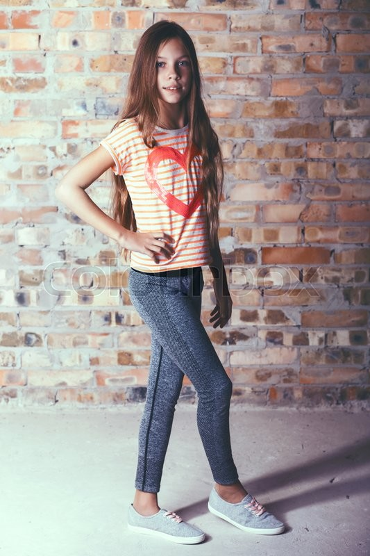 Fashion pre teen girl dressed in sports wear and sneakers posing over brick wall, stock photo