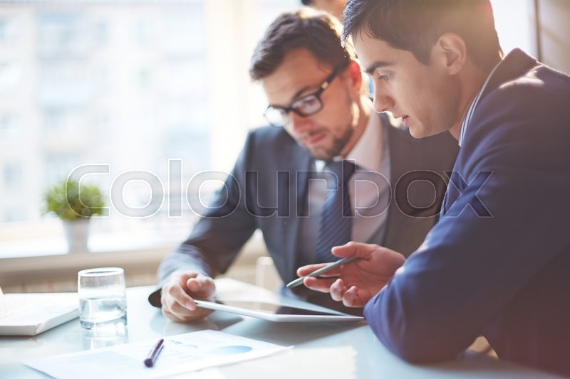 Young businessmen discussing data at meeting, stock photo