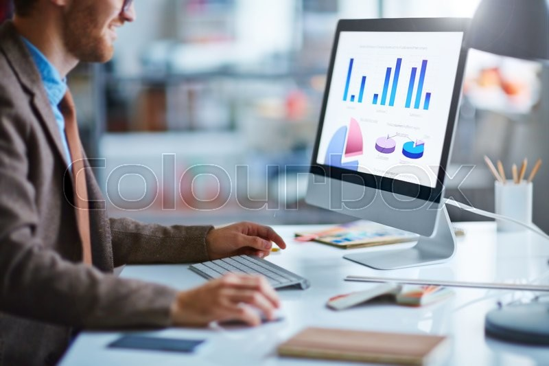Young businessman working with electronic document in computer, stock photo