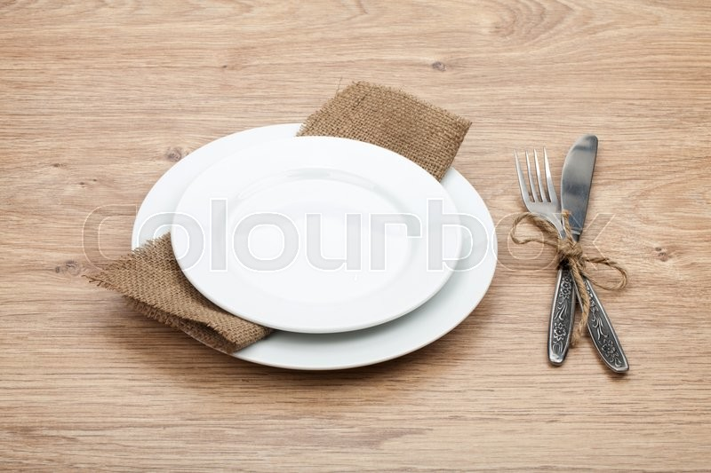 Empty plate and silverware set on wooden table, stock photo