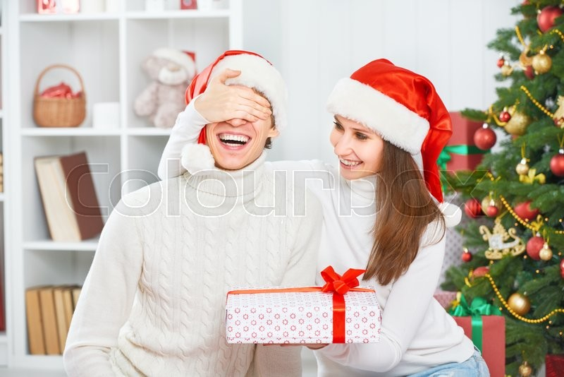 Christmas gift. woman gives a man a surprise gift present box , stock photo