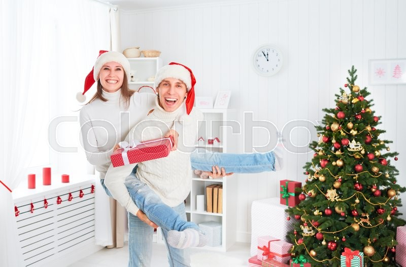 Happy funny cheerful family couple plays the fool and having fun on Christmas at home , stock photo