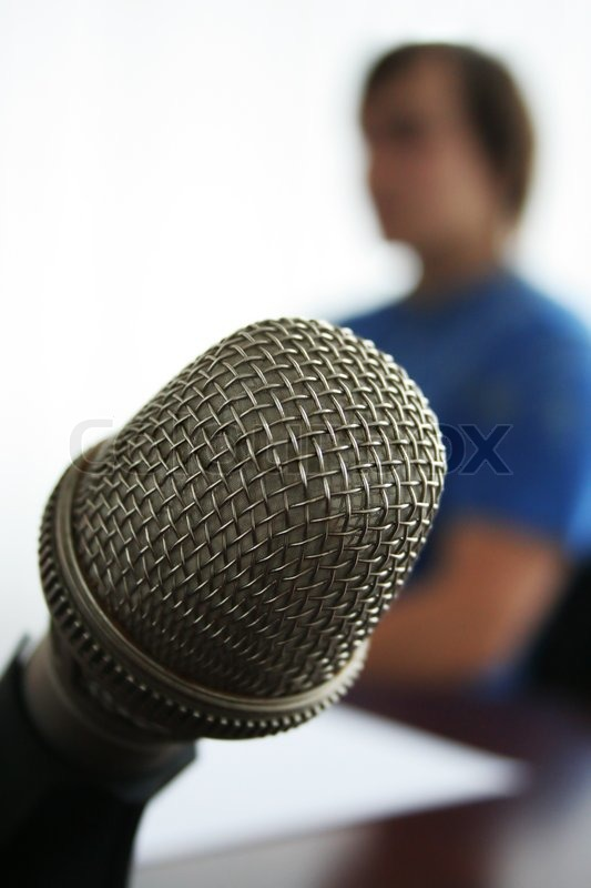 Microphone in the foreground in radio studio, stock photo