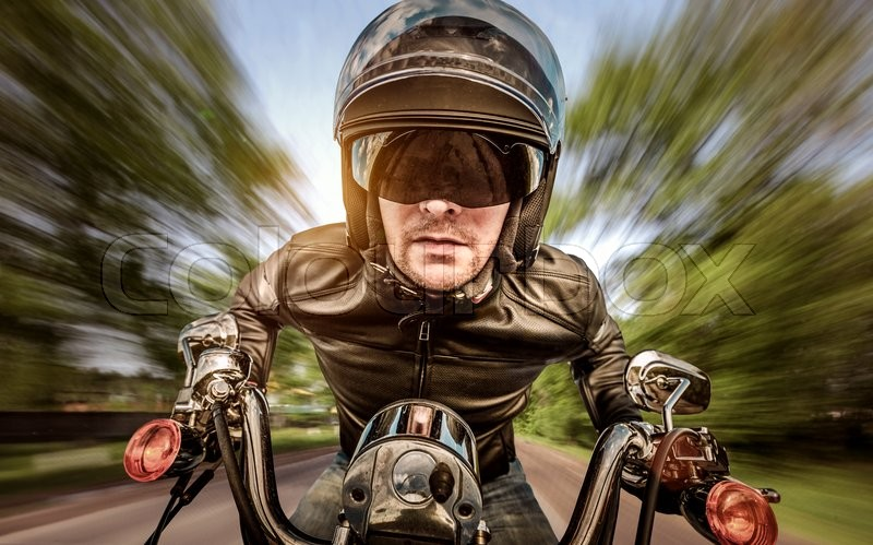Biker in helmet and leather jacket racing on the road, stock photo