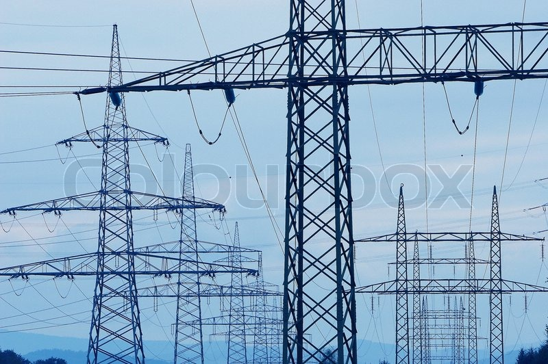 A receding line of steel pylons supporting power transmission lines, stock photo