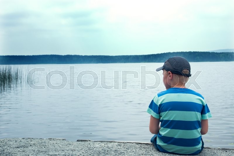 sad child sitting alone at the lake on a cloudy day back view