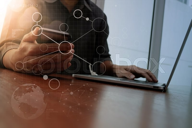Designer hand working and smart phone and laptop with social media diagram on wooden desk in office, stock photo