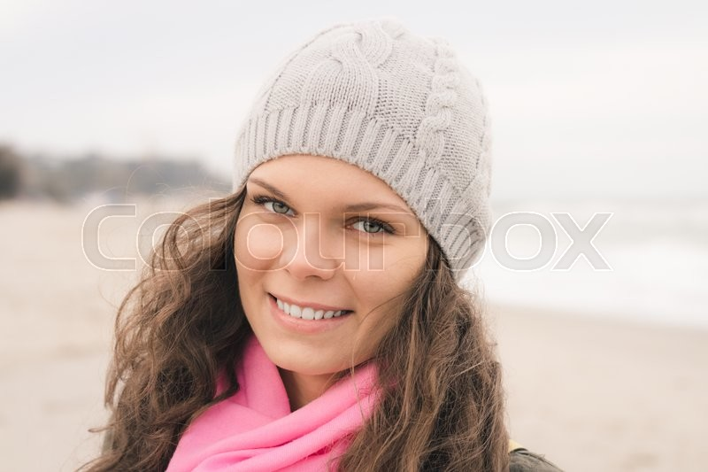 Portrait of a smiling woman in a gray coat and a pink scarf in the fall on the beach, stock photo
