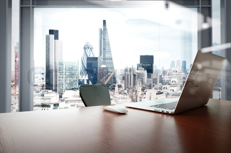 Office workplace with laptop and smart phone on wood table with london city background , stock photo