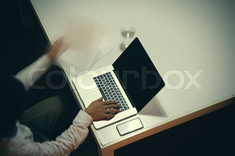 Top view of man working with business documents on office table with digital tablet and man working with smart laptop computer, stock photo