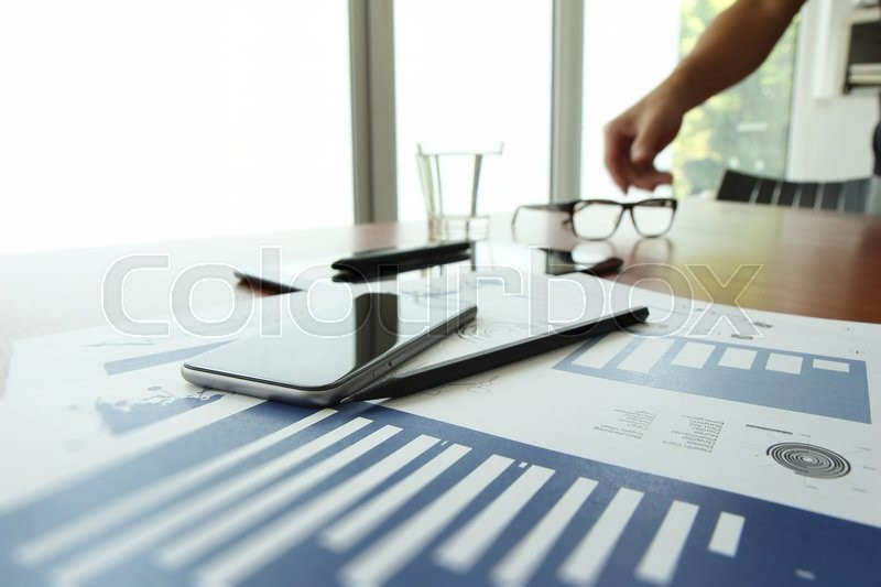 Business documents on office table with smart phone and digital tablet and man working in the background, stock photo