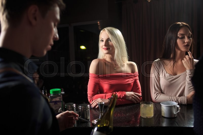 Handsome bartender serving cocktail to ... | Stock image | Colourbox