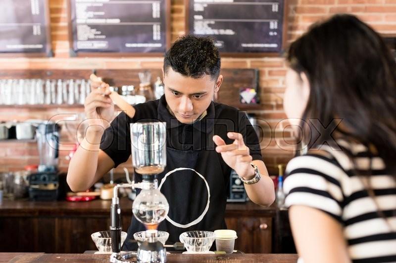 Woman watching barista preparing drip coffee in cafe, stock photo