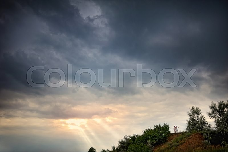 Couple in a landscape, storm clouds and sun beam, stock photo
