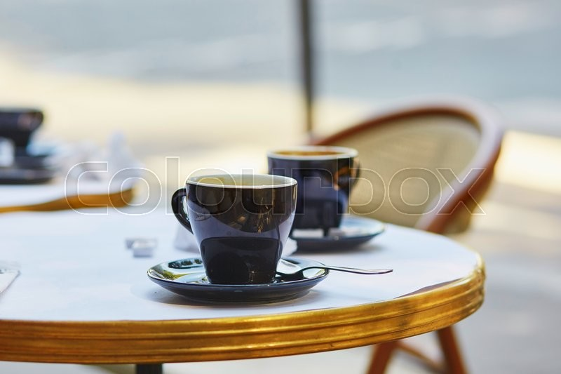 Coffee cups in an outdoor Parisian cafe, stock photo