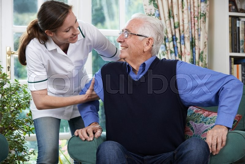 Care Worker Helping Senior Man To Get Up Out Of Chair, stock photo