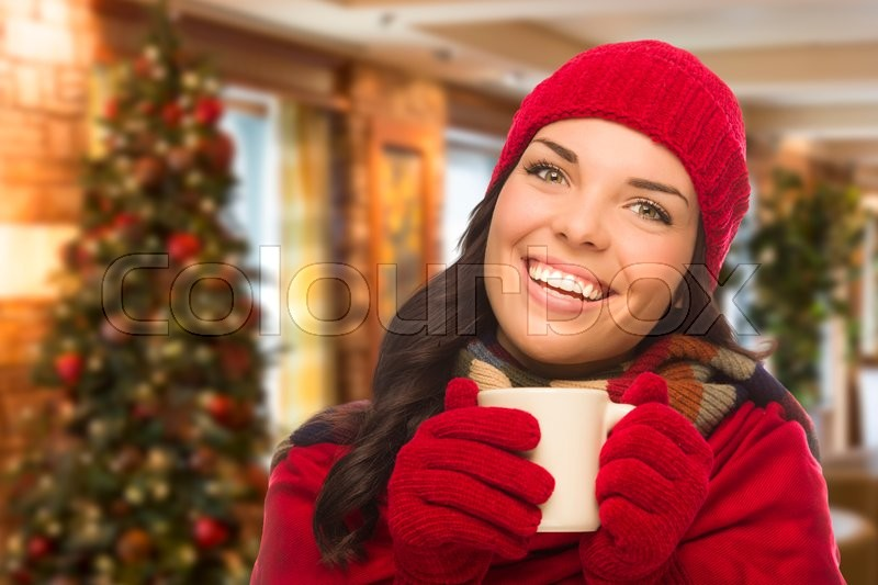 Warm Mixed Race Woman Wearing Winter Hat and Gloves In Christmas Setting, stock photo