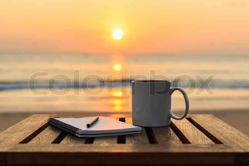 Close up coffee cup on wood table at sunset or sunrise beach, stock photo