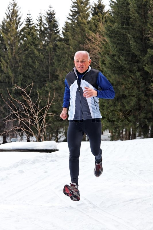 Seniors country skiers in winter on snow while jogging, stock photo