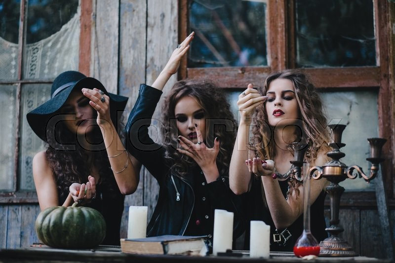 Three vintage witches perform magic ritual, throwing sweet at a table on the eve of Halloween, stock photo
