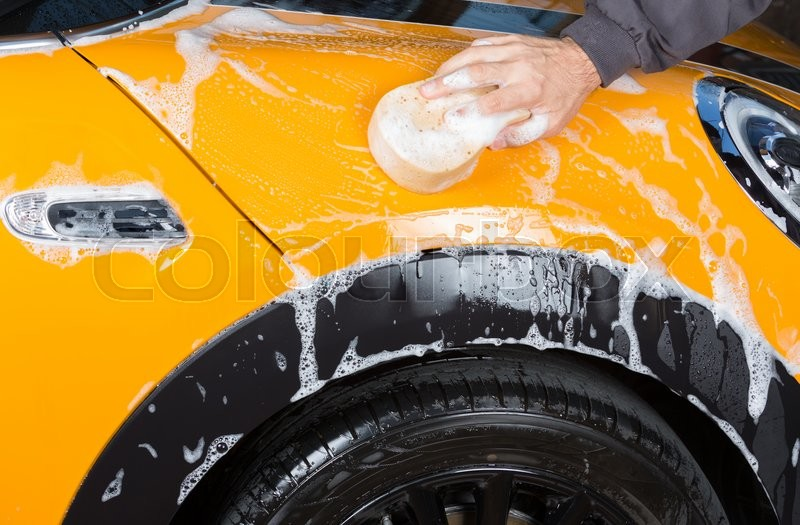 Stock image of 'Washing a car with water and yellow hand soap'